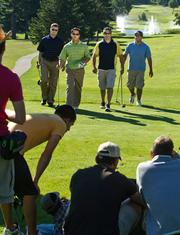 From left, Matt Huebsch, Blake Siewert, Aaron Crocker and Chris Metcalf walk towards the camera during production of a Wisconsin Department of Tourism commercial at the House on the Rock Resort golf course near Spring Green.