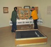 Workers remove the painting from the crate.