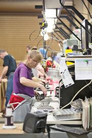 Worker Bonnie Reilly handles parts at the metal stamping and fabrication company.