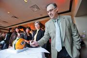 Tom Frederick of Wells Fargo bids on an autographed helmet.