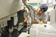 Student Shaun Wanzo inspects a CNC Swiss machine.