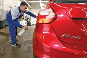 Lot attendant Nick Gray prepares a car at the Heiser Ford Lincoln dealership.