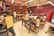 Young girls learn how to use sewing machines in a clothing design class.