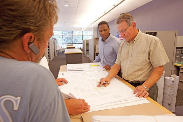 Burgess McMilan (left) and Tom Cottreau examine mechanical plans at the city Development Center.