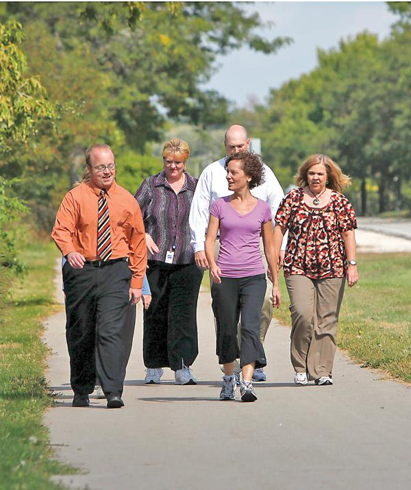 Lynn Jack, center, takes a walk with a group of North Shore Bank employees. What's Your Routine? Company: North Shore Bank Headquarters: 15700 W. Blue Mound Road, Brookfield Employees: 500 (175 at corporate office; 325 at 45 branches) Routine: On-site workout classes including yoga, tai chi and Zumba; 10-week walking club, weight loss programs, CPR training, chair massages, self-defense training