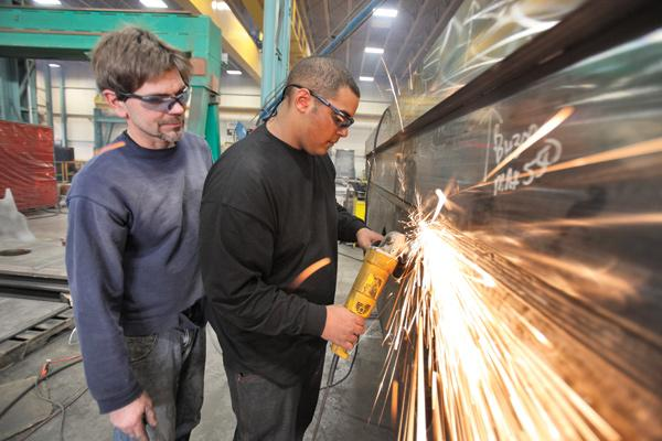 Monarch Machining & Fabrication supervisor Tim McLaughlin (left) oversees work by Alexander Tate, a senior at Menomonee Falls High School. Tate, who is in his second rotation at Monarch, does a variety of tasks, including welding, grinding and working on the burning table.