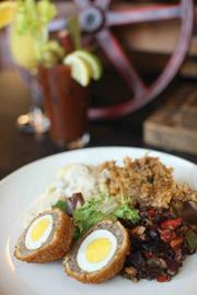 Scotch eggs features bourbon-marinated hard boiled eggs wrapped in sage breakfast sausage and a golden brown breading.