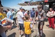 IndyCar driver J.R. Hildebrand signed autographs for racing enthusiasts on the track.