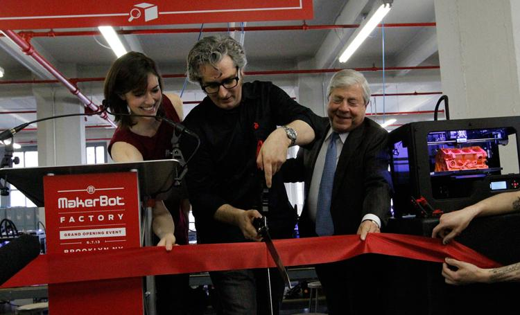 MakerBot Industries co-founder Bre Pettis, shown at center cutting the ribbon on a new Brooklyn, N.Y.-based factory on June 7, will remain with the company and run it as a separate subsidiary now that it has been acquired by Stratasys.