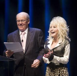 Herschend Family Entertainment, Dolly Parton's operating partner with Dollywood Co., will not pursue a Nashville water park without Parton's involvement. Pictured: Parton and Ryman Hospitality Properties' Colin Reed.