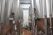 Hans Johnson, a brewer at Blackstone Brewery, cleans up around the fermenting tanks.
