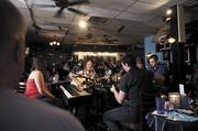 """Singer-songwriters Heidi Burson, Dennis Lee, Matt Martino and Dan Hageman (left to right) perform for a full house at the Bluebird Cafe. The famous venue has been replicated as a studio set for the production and filming of ABC's """"Nashville"""" show. Bluebird general manager Erika Wollam Nichols is hoping the increased visibility translates to increased business."""