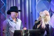 Dolly Parton and Kenny Chesney prepare to present the Entertainment Achievement Award to Joe Galante.