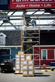 Workers construct a stage for entertainment to be used before and during games at LP Field Wednesday.