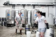 Jackalope co-owner Bailey Spaulding move kegs to be cleaned while Steve Wright works on the brew.