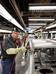 Nima Farzaneh works a buffer on the production line at the Nissan North