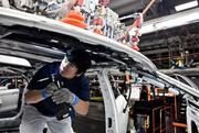 Nunu Noravong manages a machine that levels out the sunroof at the