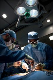 Cardiac Surgeon Dr. V. Seenu Reddy wraps up his portion of the surgery, with the support of registered nurse Gracie Keller andCertified First Assistant Dan Lenigan.