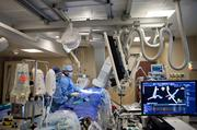 Ashley Crane and Dr. Greg Bashian are supported by staff and multiple monitors and devices in their procedure.