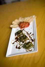 Grilled grape-leaf-wrapped goat cheese with marinated roasted bell peppers, pomegranate reduction and crostini. $8