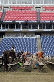 Volunteers working with Spring To Life Ministries in Murfreesboro set up and clean chairs in LP Field in preparation for the CMA festival.