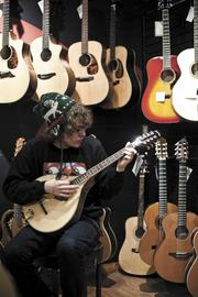 """Customer Nathan Duncan tests an octave mandolin at Corner Music. """"They have the most friendly staff. People here are insanely helpful,"""" he said."""