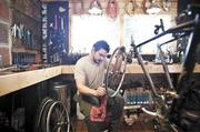 Service Manager Dan Allen works on a tire and chain repair at Halcyon Bike Shop in the 12th Avenue South business district.