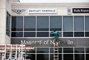 Kenneth Stephens of Lewis Glass Co. installs windows at the Maserati Rolls-Royce Bentley of Nashville dealership in Franklin.