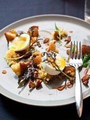 The Salad Lyonnaise at Flyte includes bacon lardons, warm egg, buttermilk cornbread and hot sauce.