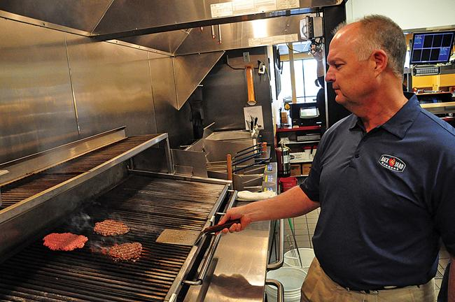 Bob Page flips hamburgers at the Back Yard Burgers Hermitage Grill. Page is CEO of the Nashville-based burger chain, which is launching a new format to compete with premium burger restaurants like Five Guys.