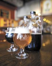 """""""The Rose,"""" center, next to a sample of """"The Fortress"""" by Black Abbey Brewing Co."""