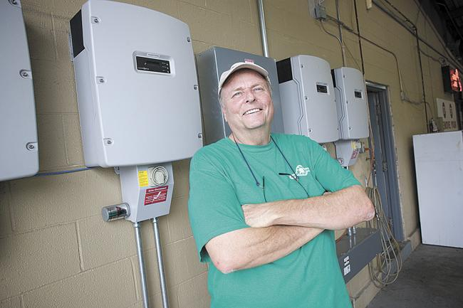 White Bridge Auto Wash owner Karl Peters is an early adopter of solar energy at his business. He is standing in front of the inverters that transform solar power into alternating current.