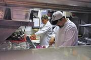 The Yellow Porch cooks Pedro Villalobos, right, and Jose Angeles prepare for the night's dinner service. Many restaurants are figuring out how to deal with rising food costs after the worst drought in nearly 50 years. Many local restaurants are changing menus to avoid raising prices.