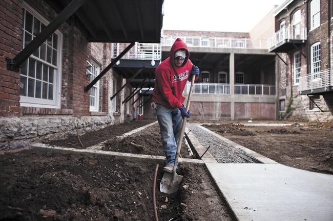 Steven Schafer digs a trench for landscape lighting as development continues at the historic Werthan Mills in Germantown, where developers are now planning a $40 million, 282-unit apartment project.