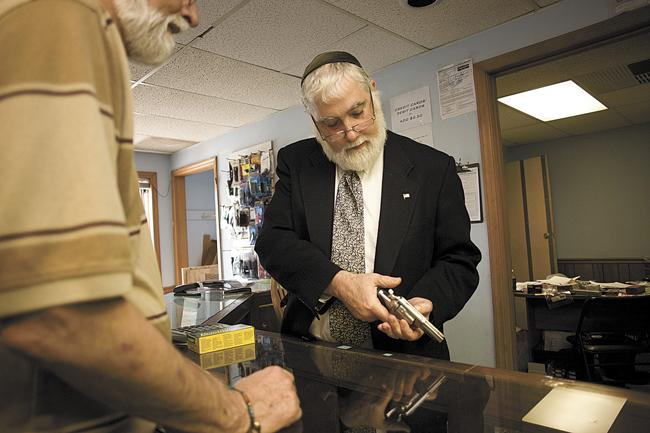 Bill Bernstein, owner of East Side Gun Shop, shows a .38-caliber revolver to customer Jay Watson. The state of Tennessee, like much of the country, has seen a major increase in the sale of firearms.