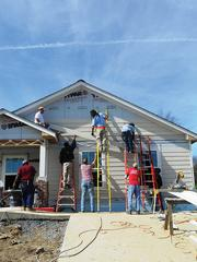 Volunteers from YouthBuild USA, YMCA of Middle Tennessee and 1st Church Unity hang siding at a Habitat house with the help of onsite supervisor Steve Lainhart.