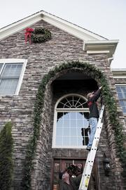 Ted Williams and Tom Jones decorate the house of client Kevin Blood in Brentwood with Christmas lights and wreaths.