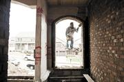 """Jaime Hernandez of Carlos Roofing cleans mortar from an archway on a home under construction in Burkitt Place in South Nashville. """"Things are selling very fast,"""" said David McGowan, president and owner Regent Homes."""