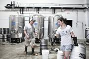 Jackalope co-owner Bailey Spaulding moves kegs to be cleaned while Steve Wright works on the brew.