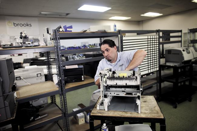 Troy Chandler works on a printer at TotalPrint. The company, which provides software that remotely monitors printers and copiers, recently bought Brooks Technology Management to continue expanding its business.