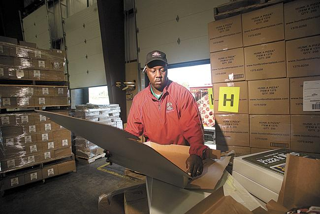 Rodney Monie, a warehouse assistant at the Hunt Brothers Pizza facility in Nashville, prepares promotional materials for shipping.