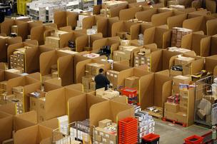 An employee selects goods from storage units ahead of packaging for delivery at the Amazon.co.uk Marston Gate 'Fulfillment Center,' the U.K. site of Amazon.com Inc. in Ridgmont, U.K., on Monday, Dec. 3, 2012.