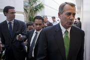House Speaker John Boehner, a Republican from Ohio, right, walks out of a House Republican caucus meeting at the U.S. Capitol in Washington, D.C., U.S., on Tuesday, Jan. 1, 2013. The U.S. Senate passed a bipartisan budget deal two hours after income tax cuts expired, reaching an after-deadline agreement to undo the potential economic harm of $600 billion in tax increases.