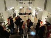 Workers enter the storm-damaged South Ferry subway station. The MTA estimates it could take up to three years and $600 million to rebuild.