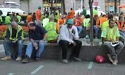 Construction workers amid their daily routine rebuilding the World Trade Center pause to take a break at Zuccotti Park, the former site of the protest's tent-city.