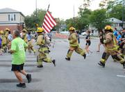 Firefighters run with the flag at the IOA Corporate 5K.