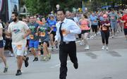 A runner in business attire keeps up with the crowd at the IOA Corporate 5K.