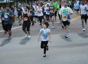 A younger runner keeps up with older competitors IOA Corporate 5K.