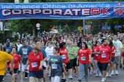 A continuous stream of runners and walkers pass the starting line of the IOA Corporate 5K.