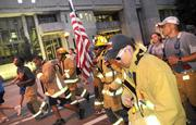 The flag carrying firefighters make their way to the finish line at the end of the IOA Corporate 5K.
